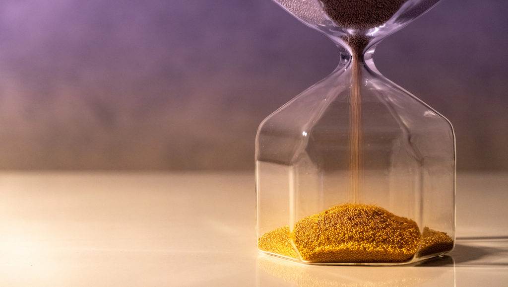 Brown sand emptying into bottom of hour glass, purple background