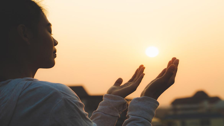 Woman holding hands up in prayer inspiring believers inspire