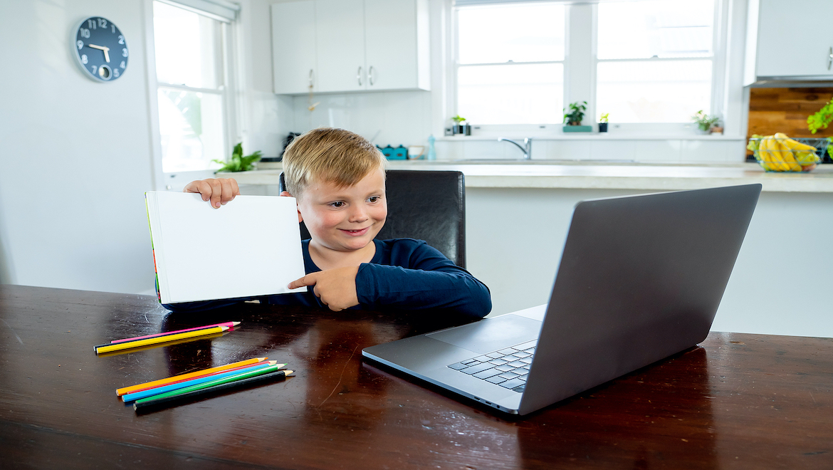 child sitting at table for online school with laptop