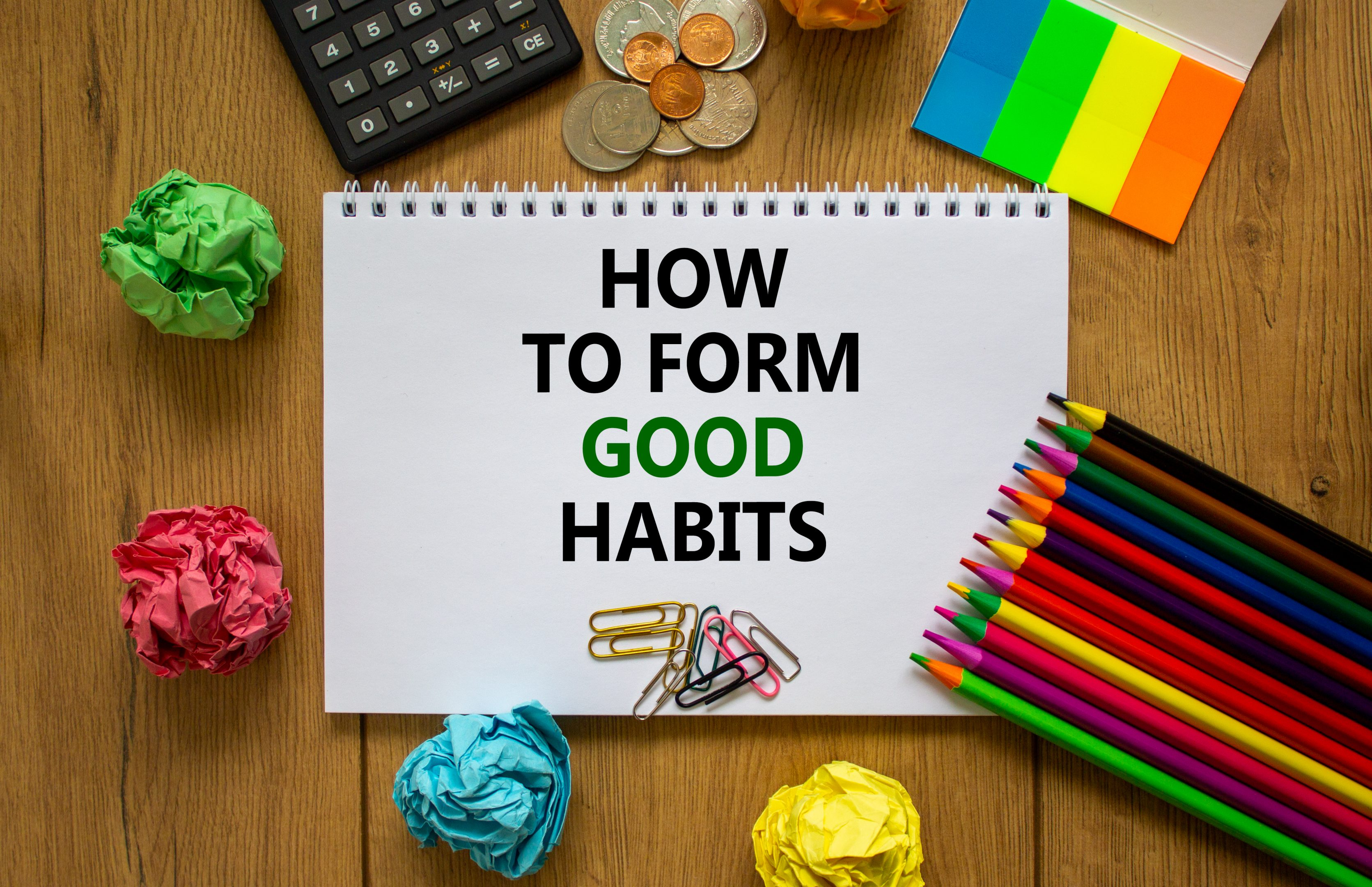How to Form Good Habits is written on a piece of paper, surrounded by colored pencils, a calculator, and crumpled colored paper.